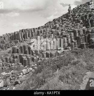 Degli anni Cinquanta, storico, un gentleman sorge sulla sommità di antiche rocce vulcaniche e colonne di basalto presso l'unico Giant's Causeway, Co Antrim, Irlanda del Nord.