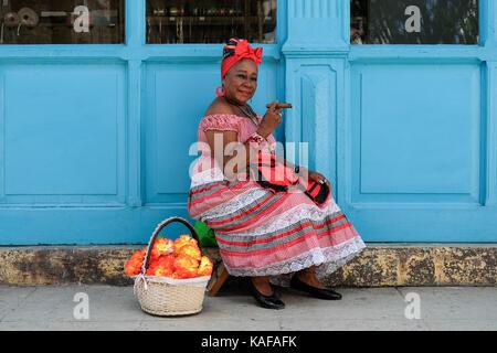 Un colorfully vestito donna cubana in abiti tradizionali si siede sulle strade di Habana vieja a l'Avana, Cuba. Foto Stock