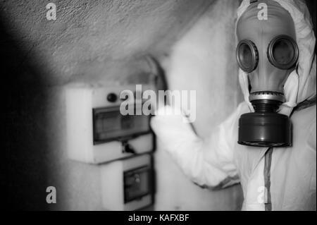 Uomo con una maschera a gas e a prova di gas abito - Rischio chimico - COMANDO GAS EFFETTUATA DAL TECNICO - PERICOLO Foto Stock