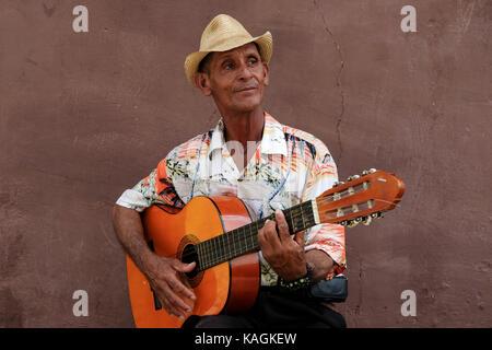 Un uomo cubano svolge la sua chitarra sul lato di una strada nel centro della città di Trinidad, Cuba. Foto Stock