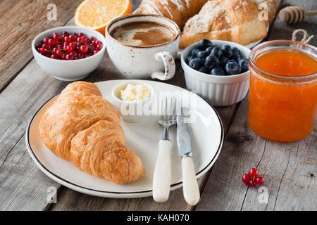 La prima colazione continentale cornetti freschi con burro, tazza di caffè, marmellata e frutta su un tavolo di Foto Stock