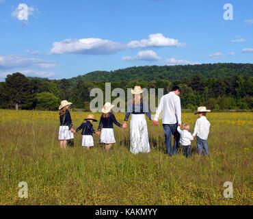 Mamma e papà portano i bambini attraverso il campo aperto di fiori gialli in Alabama rurale. tutti si tengono per mano. Foto Stock