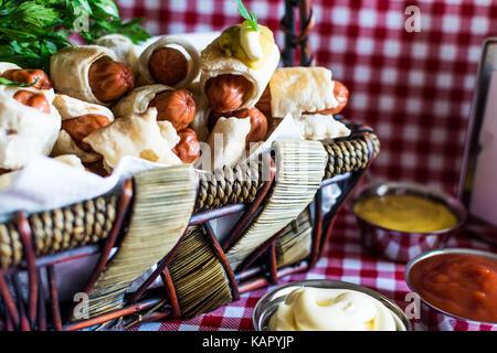 Cesto in Vimini con artigiano mini hot dogs (salsiccia nell'impasto) con senape, maionese su un plaid sfondo Foto Stock