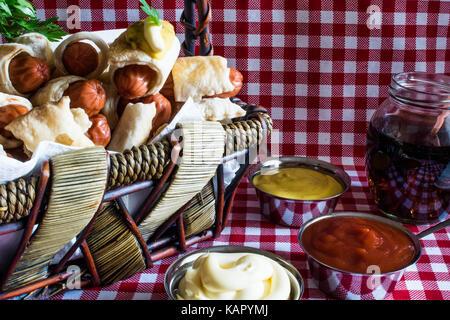 Cesto in Vimini con mini artigiano hot dogs (salsiccia nell'impasto) con senape, maionese e cola su un plaid sfondo Foto Stock
