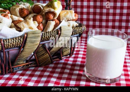 Cesto in Vimini con mini artigiano hot dogs (salsiccia nella pasta) e un bicchiere di latte vaccino fresco del villaggio Foto Stock