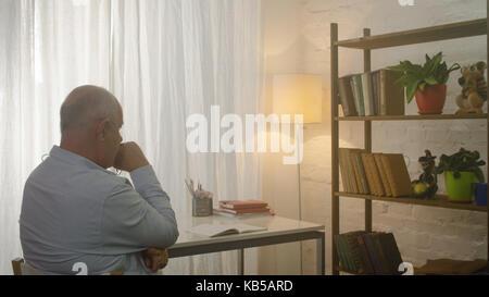 Riflessivo uomo senior in salotto. triste vecchio seduto al tavolo Foto Stock