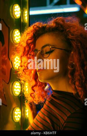 Ritratto di una giovane donna di notte illuminato con luci di colore Foto Stock
