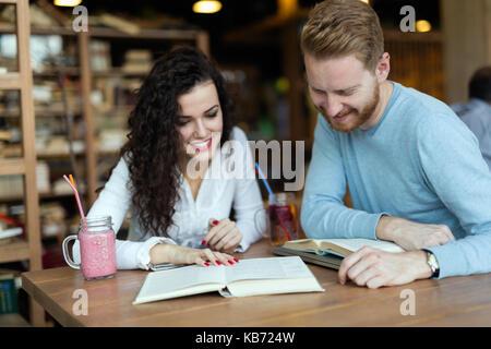 I giovani studenti di trascorrere del tempo in un coffee shop libri di lettura Foto Stock