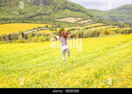 Retro della giovane donna la corsa, il salto in aria e sorridente sulla campagna giallo tarassaco campi di fiori Foto Stock