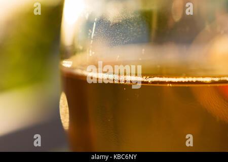 Close-up di vetro con dei deliziosi piatti greci vino Retsina e bolle durante il tramonto Foto Stock