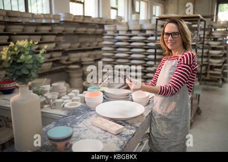 Ritratto di donna potter con tavoletta digitale nel laboratorio di ceramica