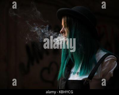 Emo girl Sigaretta fumare.street punk o hipster donna con colorate blu capelli tinti, cappello, piercing,lenti,orecchie Foto Stock