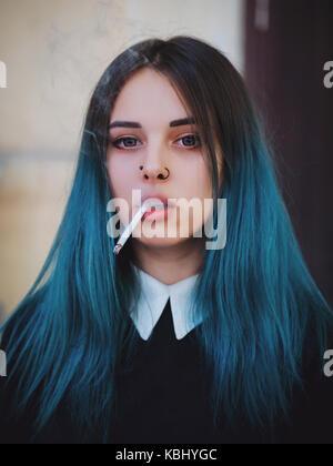 Emo girl il fumo di sigaretta. giovane studente o alunno con colorate blu capelli tinti, cappello, piercing,lenti,orecchie Foto Stock