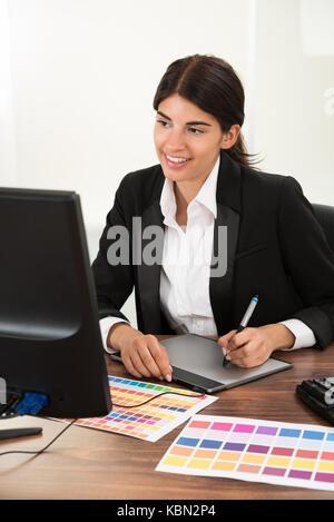 Designer femmina con tavoletta grafica con colori campione a scrivania Foto Stock