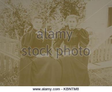 American archivio foto in bianco e nero di due giovani donne seduti in un giardino amaca con le mani incrociate Foto Stock