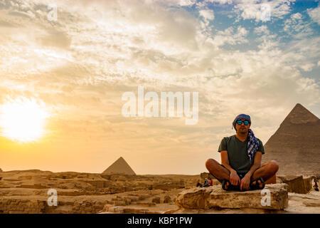 La meditazione vicino alle piramidi del Cairo in Egitto Foto Stock