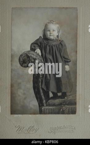 Archivio americano monocromatico ritratto in studio fotografia del bambino in piedi su una chaise longue divano, Foto Stock