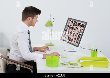 Giovane imprenditore editing delle immagini sul computer in ufficio Foto Stock