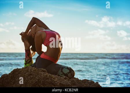 La meditazione sul Cielo di tramonto sfondo. giovani attiva donna sit in yoga pone sulla roccia spiaggia, stretching per mantenere la forma e la salute. Uno stile di vita sano. Foto Stock