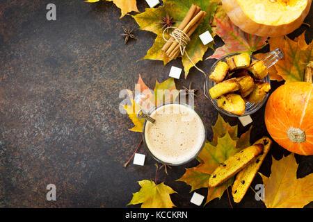 Pane appena sfornato uvetta e cannella biscotti e una tazza di caffè cappuccino su una cucina un tavolo di legno. Foto Stock