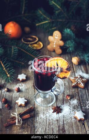 Vin brulé in vetro con mirtilli rossi e spezie decorato con arancio bruciato. drink di natale. vacanza concetto Foto Stock