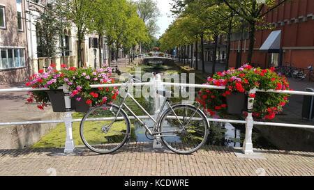 Bellissimo paesaggio urbano con bicicletta su un ponte su un canale in una piccola città in Sud Olanda. Foto Stock