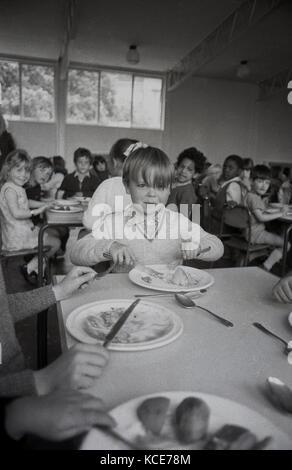Anni Settanta, storico, immagine mostra un giovane ragazzo seduto a mangiare la sua scuola cena ad un tavolo con Foto Stock