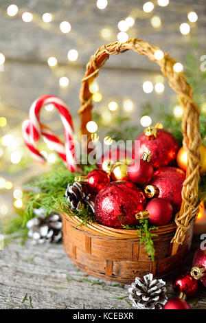 Cesto Natalizio con regali vintage e splendente di luci. Palle rosse, pigne, lecca-lecca sul tavolo di legno spazio Foto Stock