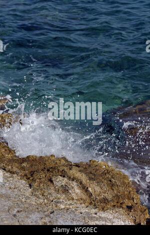 Onde che si infrangono su alcune rocce nel mar Ionio o mar mediterraneo con un mare cristallino e acquamarina su Foto Stock