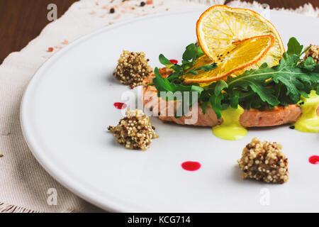Bistecca di salmone con salsa di arancio, rucola e fettine di arancia Foto Stock