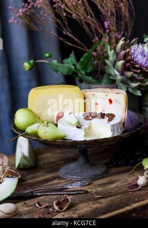 I vari formaggi, frutta fresca e fiori da giardino su uno sfondo di legno vecchio Foto Stock