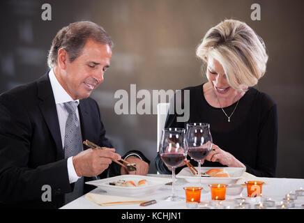 Felice Coppia matura godendo un sushi in un ristorante Foto Stock