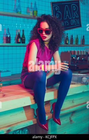 Bella donna con shot in bar Foto Stock