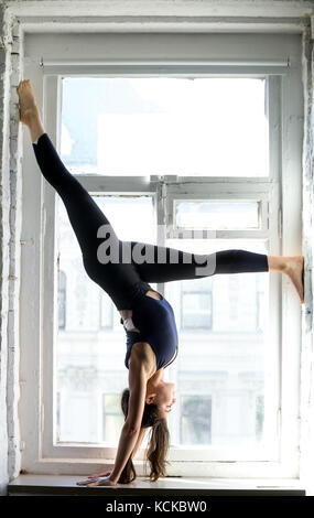 Giovane donna attraente la pratica dello yoga, in piedi adho mukha vrksasana esercizio, rivolte verso il basso la Foto Stock