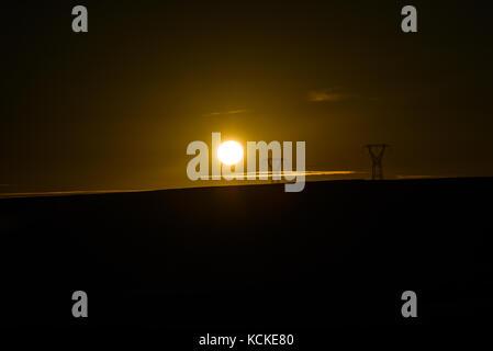 Le linee di alta tensione contro lo sfondo del sole che tramonta in Islanda. Foto Stock