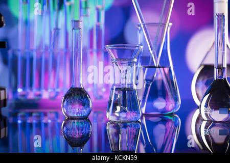 Concetto di laboratorio. Bicchieri di vetro da microscopio e provette coloful bokeh sfondo. Foto Stock