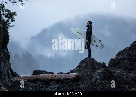 Un surfista torna al campo dopo una ricostruzione delle onde sulla costa più occidentale di Spring Island. Kyuquot, Vancouver Island, British Columbia, Canada