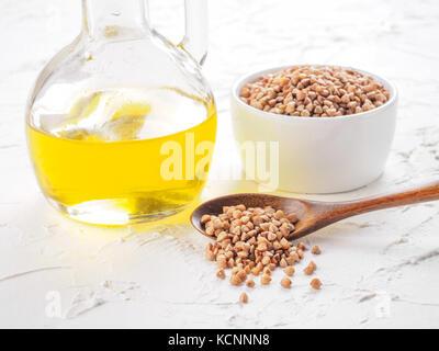 Brown del grano saraceno in cucchiaio di farina di grano saraceno e olio in bottiglia di vetro bianco su sfondo Foto Stock