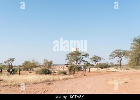 Una scena di strada con una casa ed un serbatoio di acqua in koes, una piccola città nella regione di karas in Namibia Foto Stock