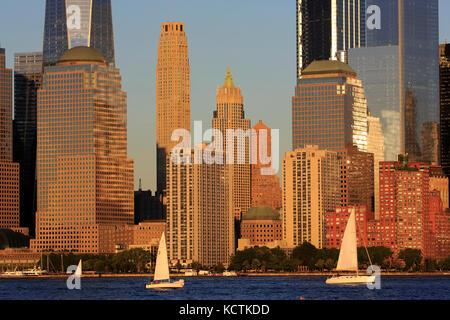 Skyline del quartiere finanziario di Lower Manhattan con barche a vela nel fiume Hudson in primo piano sotto la luce del sole del tardo pomeriggio.New York City.USA