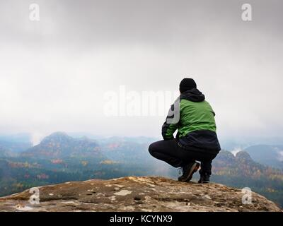 Turista nel cappuccio rosso e verde abbigliamento sportivo nero in posizione accovacciata su una roccia e godere Foto Stock