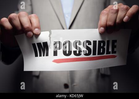 Imprenditore strappando la parola impossibile per rendere possibile un concetto per auto convinzione, atteggiamento Foto Stock