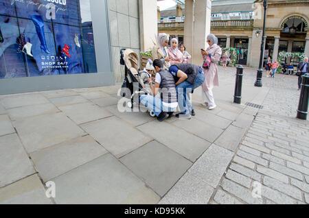 Londra, Inghilterra, Regno Unito. La famiglia musulmana in Covent Garden - gli uomini alla ricerca dopo i bambini Foto Stock