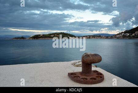 Una banchina con un bollard per la legatura e l'ormeggio delle navi nel porto di Kassiopi Corfù, Grecia al tramonto. Foto Stock