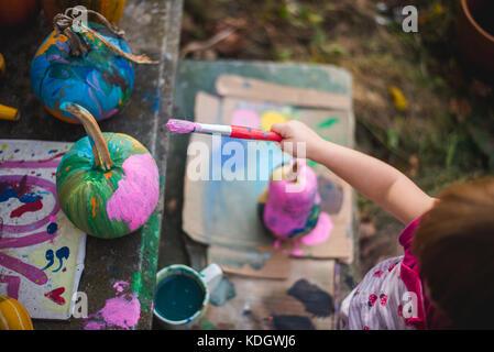 Una bambina vernici zucche durante le attività di autunno. Foto Stock