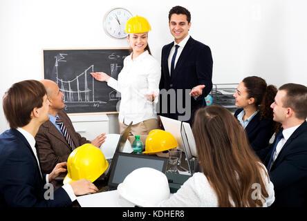 Professionisti di successo con i notebook e caschi con la presentazione del nuovo progetto in ufficio Foto Stock