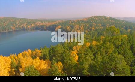 Bosco in autunno il lago in autunno vista dal cielo. Il lago di riflessioni di caduta delle foglie. antenna colorato fogliame di autunno getta la sua riflessione su acque calme. fogliame di autunno e lago di nebbia al mattino. vista aerea Foto Stock