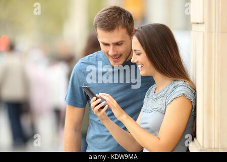 Felice casual giovane controllo contenuto in uno smart phone permanente sulla strada Foto Stock