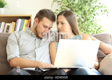 Annoiato fidanzato dormire dopo la visione sulla linea del contenuto su un computer portatile e la sua fidanzata Foto Stock