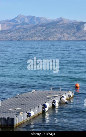 Un pontone galleggiante o molo sulla costa a Kassiopi Corfù, Grecia sul mare guardando fuori verso le montagne dell'albania Foto Stock